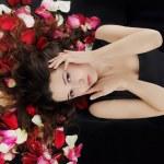Beautiful brunette in rose petals — Stock Photo #4194200