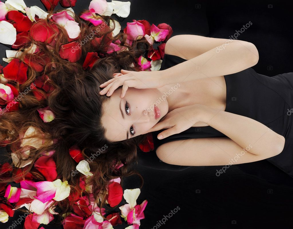 Portrait of beautiful brunette in red rose petals  Stock Photo #4194200