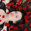Beautiful brunette in rose petals — Foto de Stock