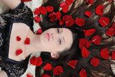 Beautiful brunette in rose petals — Stock Photo