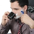 Royalty-Free Stock Photo: Businessman shaves in the workplace