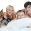 Happy family lying in bed — Stock Photo #4644032