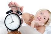 Sleepy woman turns off the alarm — Stock Photo