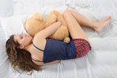 Young woman with teddybear — Stockfoto