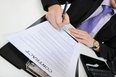 Businessman signs a contract — Stockfoto