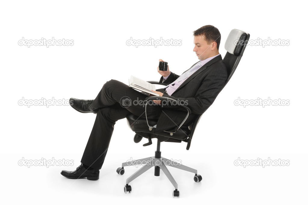Businessman reading a book and drinking coffee sitting in a chair in a bright office. Isolated on white background — Stock Photo #4851834