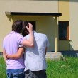 Same-sex couple next to their new house - Stok fotoğraf