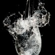 Splash in wineglass on black background - Stock Photo