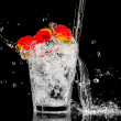 Splash in a glass with three red berry and ice on a black backgr - Stock Photo