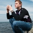 Stock Photo: Young man on the rocks on the sea background