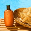 Stock Photo: Tanning lotion with sun hat by the pool