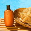 Tanning lotion with sun hat by the pool - Stock Photo