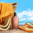 图库照片: Suntan lotion, with towel at the beach