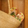 Pair of sandals hanging out of wicker purse - Stock Photo