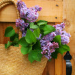 Lilacs in a straw purse — Stock Photo
