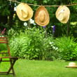 Straw hats on an old clothesline - Stock Photo