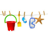 Summer toys on clothesline against white — Stockfoto