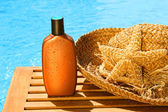 Tanning lotion with sun hat by the pool — Stok fotoğraf