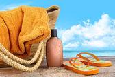Sonnenöl, mit handtuch am strand — Stockfoto