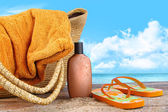 Suntan lotion, with towel at the beach — Stok fotoğraf