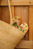 Pair of sandals hanging out of wicker purse — Zdjęcie stockowe