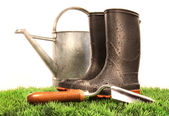Garden boots with tool and watering can — Stock Photo