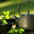 Black asian teapot with mint tea - Zdjęcie stockowe