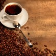 White coffee cup with beans on rustic  table - Photo