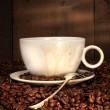 White coffee cup with spoon on roasted beans - Stock Photo