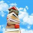 Pile of books and apple against blue sky — Stock Photo