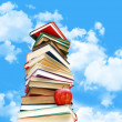 Stock Photo: Pile of books and apple against blue sky