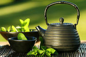 Black asian teapot with mint tea — Stock Photo