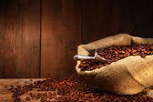 Burlap sack of coffee beans against dark wood — Stock Photo
