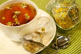 Chamomile tea with white tea cup — Stock Photo