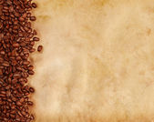 Coffee beans on old parchment paper — Stok fotoğraf