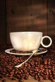 Vit kaffekopp med sked på rostade bönor — Stockfoto