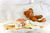 Tea in bed with teddy on white sheets — Stock Photo