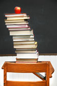 Stack of books on an old school desk — Stock Photo