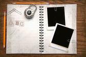 White copy book, pencils and photos — Stock Photo