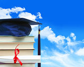 Stack of books with diploma against blue sky — Stock Photo