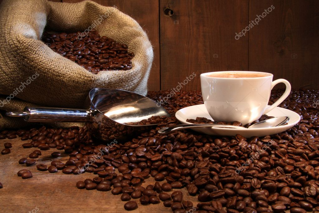 Coffee cup with burlap sack of roasted beans on rustic table — Stock Photo #3266670