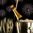 Glasses of champagne with fireworks - Stock Photo