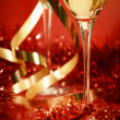 Royalty-Free Stock Photo: Fluted champagne glasses and ribbons on red
