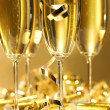Golden champagne sparkle with fluted glasses and party ribbons — Stock Photo