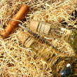 Bottles of wine laying on packing straw with cork screw — Stock Photo