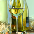 Glass of white wine with bottles on oak table - Stock Photo