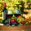 Foto Stock: Glasses of red wine on old barrel with autumn leaves