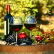Stock Photo: Glasses of red wine on old barrel with autumn leaves