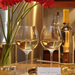 Glasses of white wine with gerbera daisies on counter in the kitchen - Stock Photo