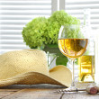 Glass of wine with straw hat on table - Stock Photo